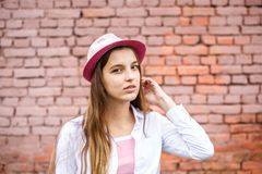 Portrait haut ?troit de belle fille ?l?gante d'enfant dans le chapeau pr?s du mur de briques rose comme fond photographie stock