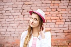 Portrait haut ?troit de belle fille ?l?gante d'enfant dans le chapeau pr?s du mur de briques rose comme fond photos libres de droits