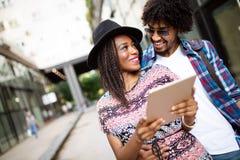 Portrait haut ?troit de jeunes couples noirs heureux utilisant un comprim? num?rique ensemble images stock