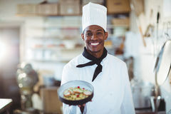 Portrait of head chef presenting salad. In commercial kitchen Stock Photos