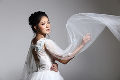 Lovely Asian Beautiful Woman bride in white wedding gown dress w Stock Photo