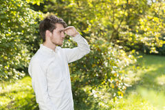 Portrait head and shoulders of bearded young man shielding eyes Stock Image
