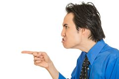 Portrait headshot angry man pointing index finger at someone. Closeup side view profile portrait headshot angry man pointing index finger at someone isolated Stock Images