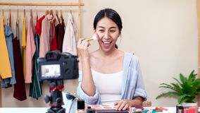 Portrait or headshot of attractive young asian influencer, beauty blogger, content creator or vlogger girl review make up looking. At camera at home. Asian stock photo