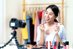 Portrait or headshot of attractive young asian influencer, beauty blogger, content creator or vlogger girl review make up looking