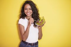 Healthy asian woman eating a bowl of salad. Portrait of healthy asian woman eating a bowl of salad on yellow background Royalty Free Stock Photos