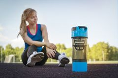 Portrait of healthy fitness girl drinking protein shake during workout on stadium. rest after morning run Royalty Free Stock Image