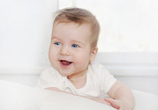 Portrait of healthy little happy baby boy lying on soft white so Stock Photos