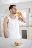 Portrait of a healthy man drinking orange juice. In his kitchen Stock Photos