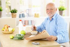 Portrait of healthy senior at breakfast. Portrait of healthy senior sitting in kitchen at breakfast, holding newspaper, looking at camera, smiling stock image