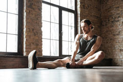 Portrait of a healthy sportsman doing stretching exercises. Portrait of a young sportsman doing stretching exercises while sitting on the floor at the gym Stock Photos