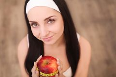 Portrait of a healthy woman with apple and measuring tape. Healt Stock Images