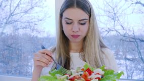 Portrait of healthy woman with plate of fresh vegetable salad on background window. Indoors stock video