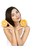 Portrait of Healthy Woman with Two Halves of Orange in Hands on White Background. Nice Girl with Perfect Skin and Long Dark Hair is Holding Fruits near her stock photography