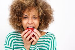 Healthy young african american woman biting an apple royalty free stock images