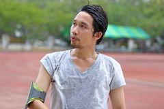Portrait of healthy young fitness Asian man after run on track in the stadium royalty free stock image