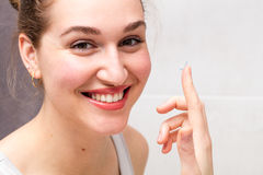 Portrait, healthy young woman with gorgeous smile holding contact lens Royalty Free Stock Photography