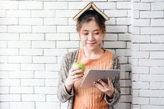 Portrait of healthy young woman holding an apple, book on head w. Hile reading tablet with happiness smile and concentrate. girl relaxing in white cozy house Stock Photo