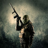 Portrait of a heavily armed masked soldier with grungy backgroun Stock Photos