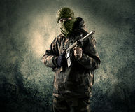 Portrait of a heavily armed masked soldier with grungy backgroun Stock Photography