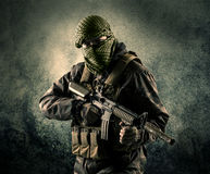 Portrait of a heavily armed masked soldier with grungy backgroun Royalty Free Stock Image