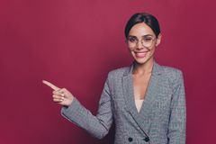 Portrait of her she nice cute sweet pretty attractive lovely winsome charming cheerful cheery lady pointing finger aside. Ad advert  over maroon burgundy stock photography