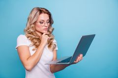 Portrait of her she nice-looking attractive focused concentrated minded wavy-haired lady in casual white t-shirt holding. In hand laptop watching video isolated royalty free stock photos