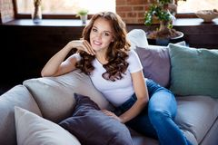 Portrait of her she nice-looking attractive sweet lovable lovely charming stylish cheerful cheery wavy-haired lady. Sitting on comfortable sofa at industrial royalty free stock photography