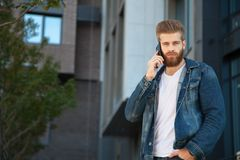 businessman talking on cell phone against office building stock photography