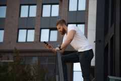 Thoughtful young modern bearded man watching to his phone in front of office building royalty free stock photos