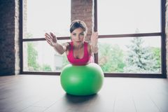 Portrait of her she nice purposeful beautiful attractive busty lady wearing pink top leaning on green fit-ball hands. Towards in modern loft industrial interior stock image