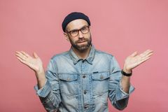 Portrait of hesitant bearded male with doubtful expression, shrugs shoulders, wears denim jacket, glasses and hat, isolated over royalty free stock images