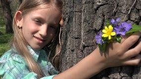 Portrait heureux d'enfant jouant en parc, visage de fille avec des fleurs de ressort en nature 4K clips vidéos