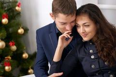 Portrait heureux de couples près d'arbre de Noël, de café potable et de parler - amour et concept de vacances Image stock