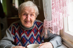 Portrait heureux de femme se reposant à la table dans le chandail Image libre de droits