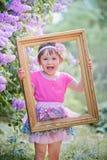 Portrait heureux de fille par le vieux cadre Photos stock