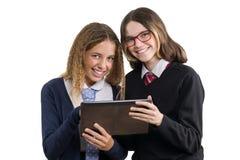 Portrait heureux de plan rapproché d'amis de lycée Des adolescentes dans l'uniforme scolaire sur le fond blanc, avec le comprimé, Photos libres de droits