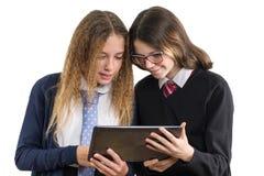 Portrait heureux de plan rapproché d'amis de lycée Des adolescentes dans l'uniforme scolaire sur le fond blanc, avec le comprimé, Photos stock