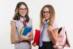 Portrait heureux de plan rapproché d'amis de lycée Posez sur l'appareil-photo, dans l'uniforme scolaire, avec des livres et des c Photographie stock libre de droits