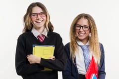 Portrait heureux de plan rapproché d'amis de lycée Posez sur l'appareil-photo, dans l'uniforme scolaire, avec des livres et des c Images libres de droits