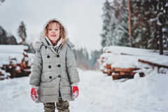 Portrait heureux drôle de fille d'enfant sur la promenade dans la forêt neigeuse d'hiver avec l'abattage d'arbres sur le fond Images stock