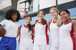 Portrait Of High School Basketball Coach With Female Team