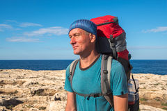 Portrait of hiker with backpack on rocky coast of sea at sunny d Stock Photos