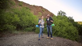 Portrait of hikers with backpacks in the mountains. Two hikers stand on the top of a mountain and enjoy valley view. Portrait of hikers with backpacks in the stock footage