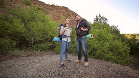Portrait of hikers with backpacks in the mountains. Two hikers stand on the top of a mountain and enjoy valley view. Portrait of hikers with backpacks in the stock video