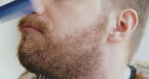 Portrait of hipster in barber shop. Close up of male beard shaved. Conception of beauty and style stock video