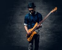 Portrait of the hipster bass player dressed in cylinder hat. Studio portrait of the hipster bass player dressed in cylinder hat Stock Images