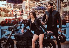 Portrait of a hipster couple - young sensual girl sitting on his custom-made retro motorcycle and a bearded brutal male. Dressed in a black leather jacket royalty free stock image