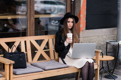 Portrait of a hipster girl dressed in stylish clothes posing while sitting with net-book on a cozy bench in sidewalk cafe Stock Photography