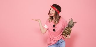 Portrait of hipster girl in glasses and pineapple on pink background royalty free stock image